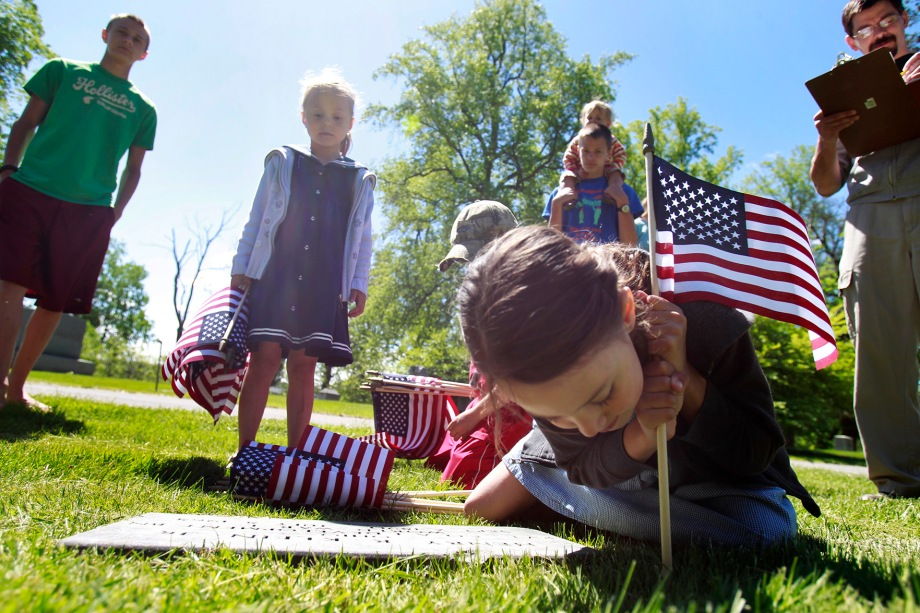 Molly Baldwin, 8, leans in to place a flag at Historic Woodlawn Cemetery in Toledo, Ohio, on Friday, May 23, 2014. She is joined by siblings Isaac, 13, left, Margaret, 5, Mark, 6, behind Molly in a cap, and Gabriel, 15, who holds Josie, 2, on his shoulders. Placing the flags has become a tradition for the Baldwins and their dad, Anthony Baldwin, right. (ISAAC HALE | STAFF PHOTOGRAPHER)