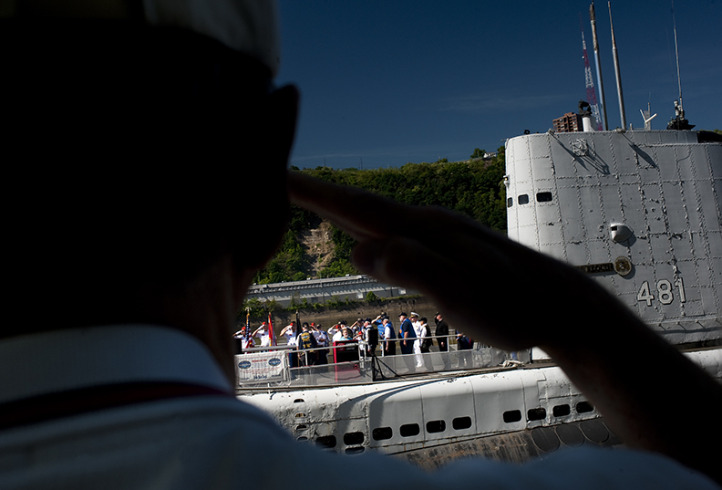 A veteran of Post 9199 salutes during the playing of the National Anthem at the start of the Memorial Day service aboard the USS Requin along the Ohio River on Sunday, May 25, 2014. (EMILY HARGER | PHOTO EDITOR)