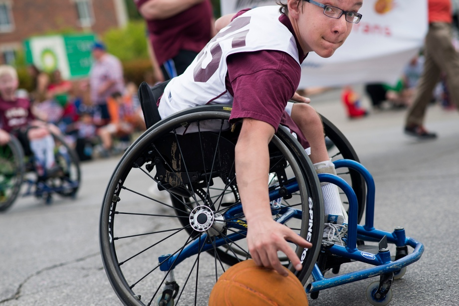 A member of the Milwaukee Heat Wheelchair Basketball team chases after a ball as the parade moves on on Monday, May 26, 2014 during the Elm Grove Memorial Day Parade in Elm Grove, Wis. (KATIE KLANN | PHOTO EDITOR)