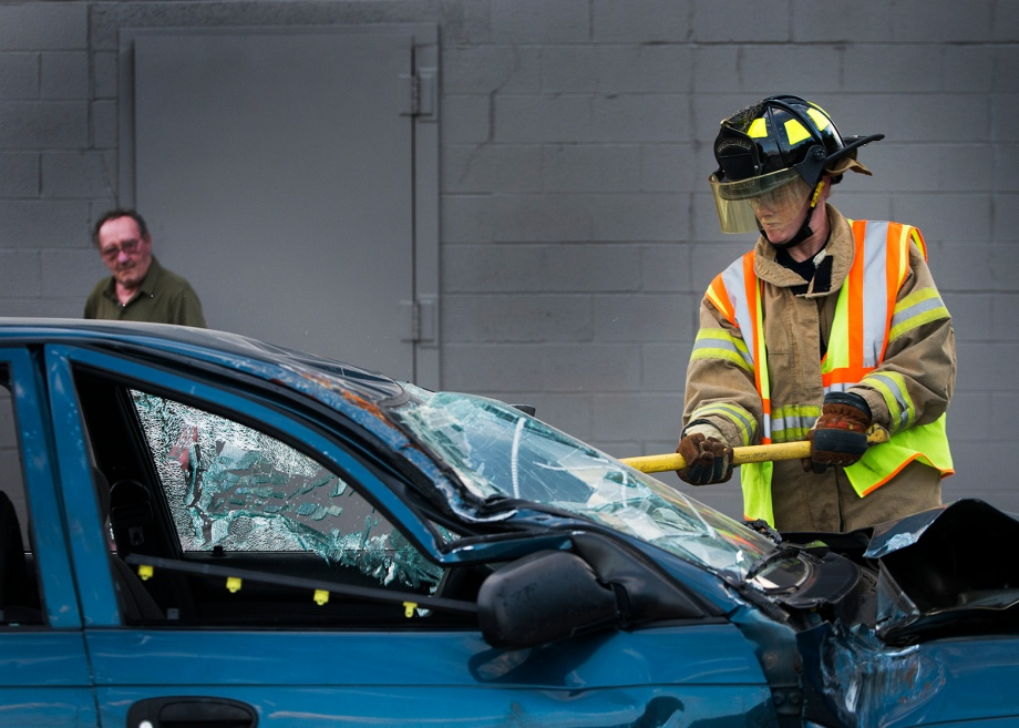 A member of the Elm Grove Volunteer Fire Department practices breaking glass on a junk car on Wednesday, June 18, 2014 in Elm Grove, Wis.