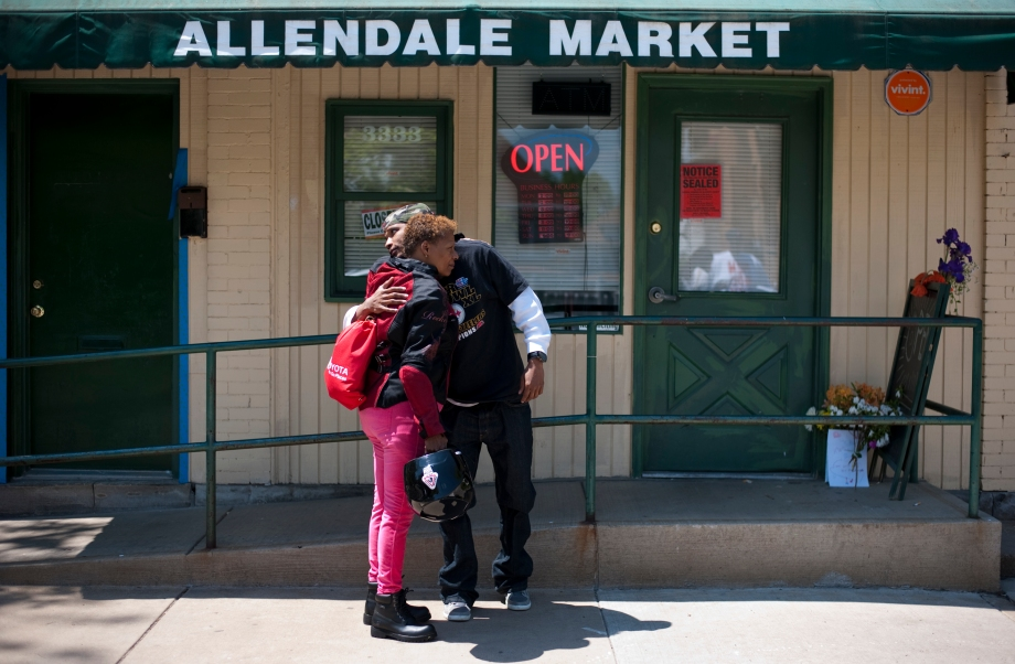 Eric Lee, landlord of the building that holds Allendale Market where  a fatal shooting took place the day before, hugs his mother Nadine Spradley outside of the market in Sheradon, Pennsylvania on May 19, 2014. Darryl Terry, the owner of Allendale Market, was fatally shot yesterday in his store. (EMILY HARGER | PHOTO EDITOR)