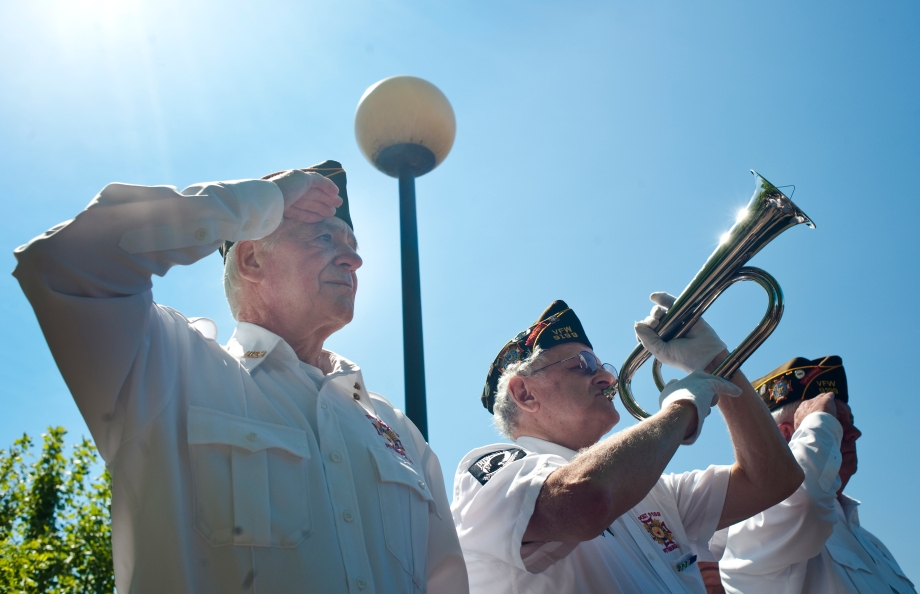 Samuel McKeown, middle, plays Taps on the bugle as Ron Luniewski, left, and John Stack, right, salute to the crowd during the Memorial Day service aboard the USS Requin along the Ohio River on Sunday, May 25, 2014. (EMILY HARGER | PHOTO EDITOR)