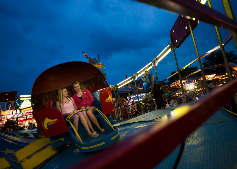 Two young girls hold on as they ride the Tilt-a-Whirl at the St. John Vianney Festival on Saturday, June 7, 2014.